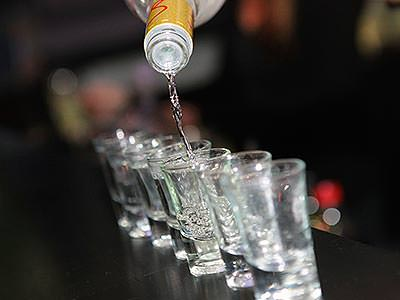 A row of shot glasses, halfway through being filled from a bottle