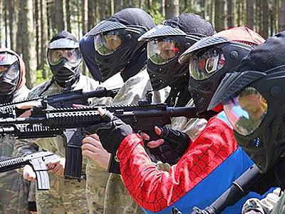 A line of people wearing overalls and full-face masks aiming AR15-style airsoft rifles