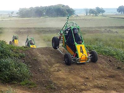A yellow and green off-road buggy landing after going over a jump on a dirt track