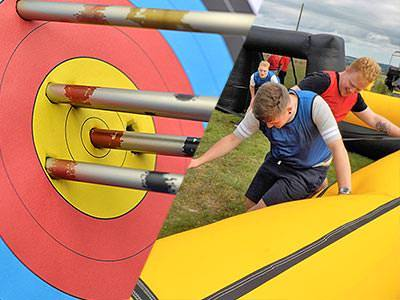 A close up of an archery target bullseye with arrows in it and a man next to a large yellow inflatable