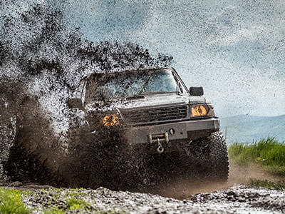 A 4x4 driving through a muddy puddle