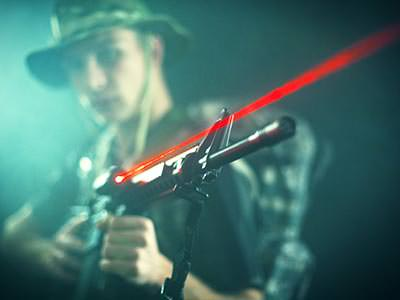 A red laser light from a laser gun with a man holding the gun