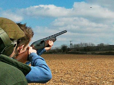 Close up of the back of a man aiming a shotgun to the sky, with a man looking on
