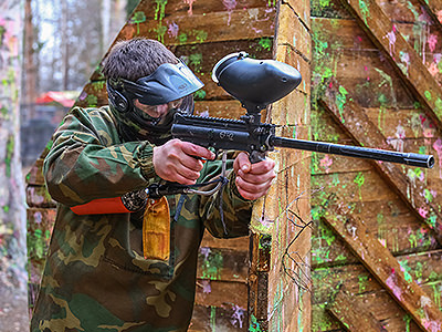A man in paintball overalls and a mask, holding a paintball gun around the corner of a fence