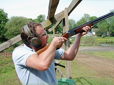 A man holding a shotgun and wearing ear muffs