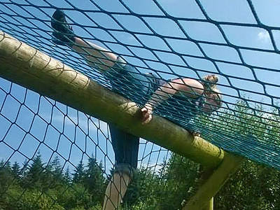 A woman clambering over a net on an assault course
