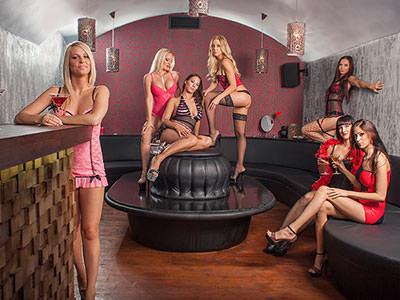 Women in different underwear posing on seats in a bar