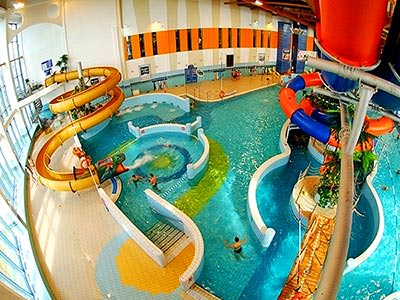 An indoor waterpark with various coloured slides leading into a pool