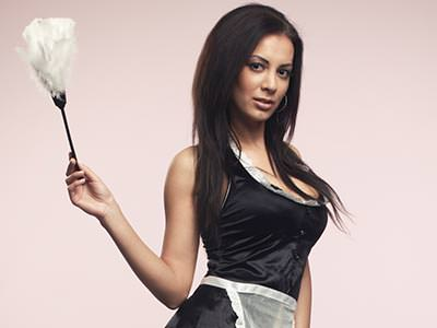 An attractive woman wearing a cleaner's outfit and holding a feather duster