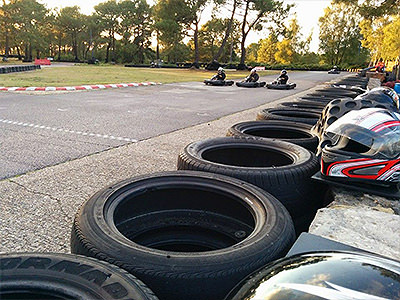 Three people driving go karts on an outdoor karting track, with tyres around the sides