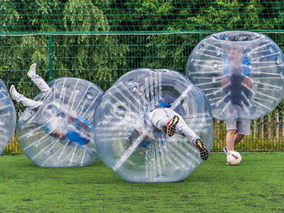 People playing in inflatable zorbs on a field