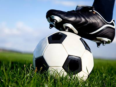 A black and white football boot on top of a black and white football in grass