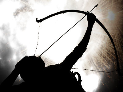 Silhouette of a man firing a bow and arrow