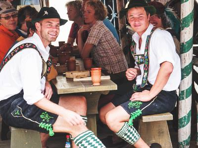 Two men wearing lederhosen, sitting at a wooden table and chairs