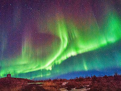 A vivid green display of Northern Lights in a starry night sky