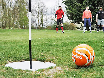 A man kicking a football on a footgolf course, with a man driving a golf buggy in the background