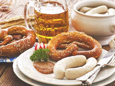 Various plates and bowls of pretzels and sausages surrounding a glass of beer