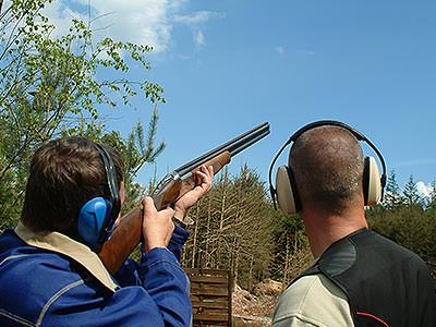 A man aiming with a shotgun to the sky, whilst another man looks on