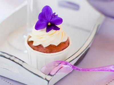 A split image of a purple cocktail and a cupcake on a white plate, with a purple flower on top