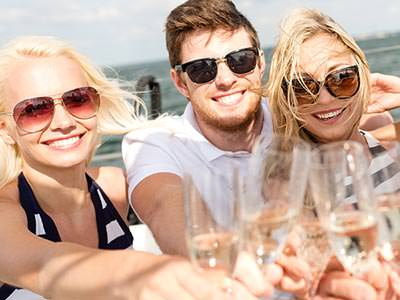 Two women and a man wearing sunglasses and clinking champagne flutes together