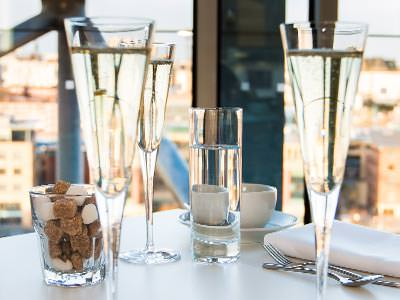 Three glasses of prosecco in focus in the foreground, to a backdrop of buildings