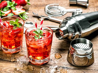 Two red cocktails and a cocktail shaker lying on a wooden table top