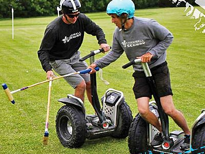 Two men riding on Segways, attempting to play polo
