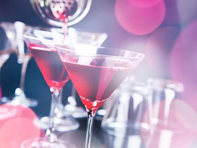 Two martini glasses being filled with red cocktail from a metal cocktail shaker