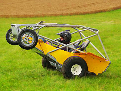A man in a yellow rage buggy on a field