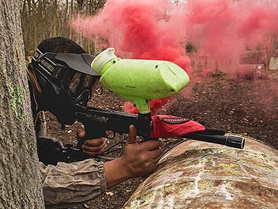 A man hiding behind a tree trunk and holding a paintball gun, with red smoke in the background