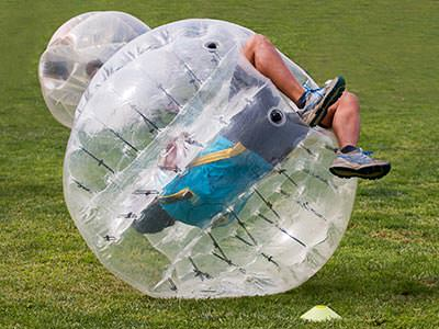 A man playing bubble football flips over with his legs in the air