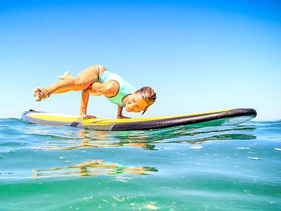 A woman balancing on her hands on a paddle board at sea