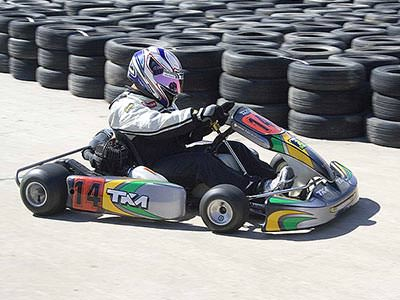 A man driving a kart on an outdoor track, in front of tyres stacked up