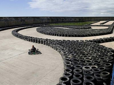 A go kart driving on an outdoor karting track, with tyres lining the sides of the track