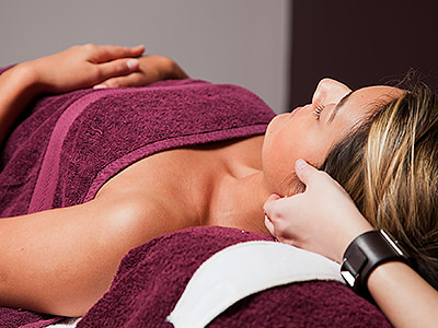 A woman receiving a massage, with a purple towel wrapped around her