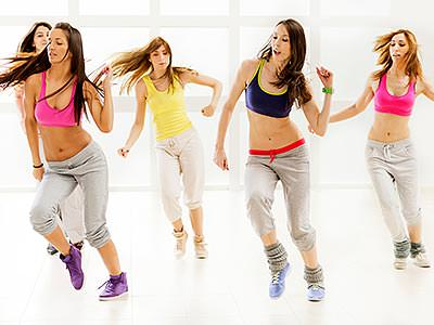A group of women dancing in tracksuit bottoms and colourful tops
