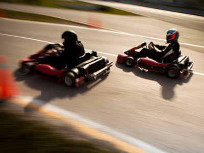 Two go karts whizzing around a track with people in black overalls driving