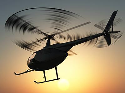 A helicopter flying at sunset