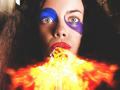 A woman with face paint on, blowing fire out of her mouth