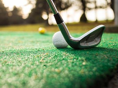 A golf club behind a golf ball on a course