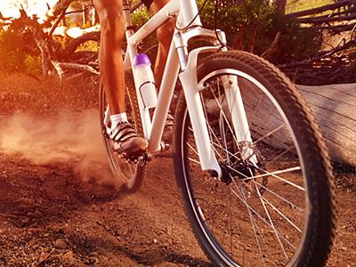 A close up of a man's legs on a white mountain bike