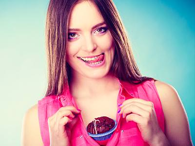 A girl licking her lips and holding a cupcake between her breasts