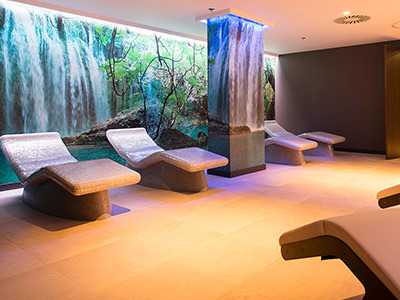 The inside of a spa with several beds and a waterfall feature background