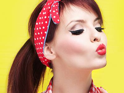 A woman wearing a red hairpiece and red lipstick, with a yellow background