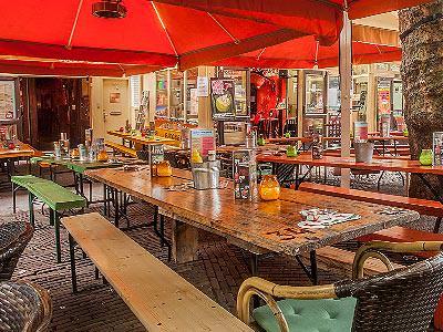Some exterior seating under red sun umbrellas
