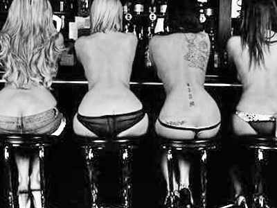Black and white image of the back of four women sat on bar stools, wearing thongs
