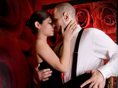 A woman dancing with a man and holding his face to a backdrop of red roses
