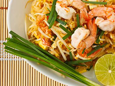 Thai noodles and prawns on a white plate
