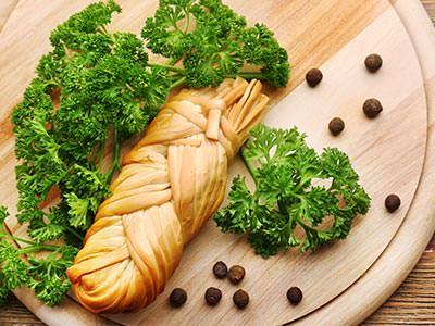 A baguette on a wooden board, served alongside green leaves
