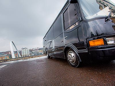 The exterior of a black party bus with the top of the Millennium Bridge in the background